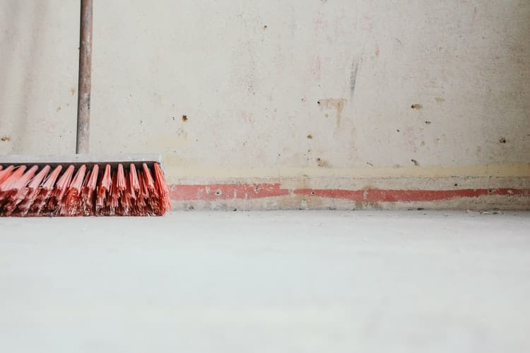 A broom leaned against a wall.